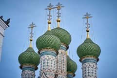 Green domes and golden crosses of an orthodox temple on the background of bright blue sky royalty free stock photography
