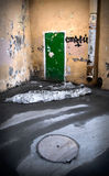 Green door. Graffiti on old yellow walls in the corner of court with sewer manhole on foreground Royalty Free Stock Images