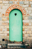Green door with a black heart. Metal door, painted in green, with a black heart Royalty Free Stock Image