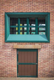 Green door color as brick wall Stock Photography