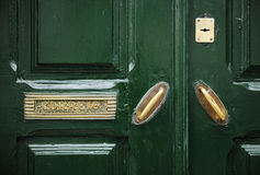 Green door with golden knobs. Royalty Free Stock Image