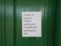 Green door with instructions how to open Royalty Free Stock Photography