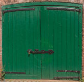 Green Door Lockup. Green doors with antique wrought iron hinges and latches Royalty Free Stock Image