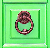 Green Door. Meta knocker on green wooden door Stock Photography