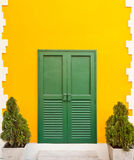 Green door in the orange wall. Background Royalty Free Stock Image