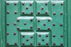 Green door with ornaments in the form of black star, background Royalty Free Stock Photos