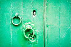 Green door. Part of an old wooden door with a latch and a ring Stock Photography