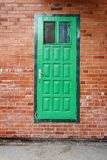 Green door on a red brick wall. Outdoor architecture with green door on a red brick wall Royalty Free Stock Photography
