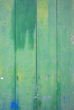 Green door with spots. Green vintage door with grungy and shabby look in green, blue and yellow Stock Images