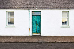 Green door and two windows on white wall house Royalty Free Stock Photography