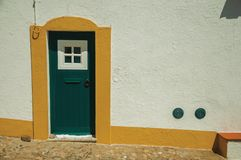 Green door on wall from a street of Evoramonte. Green wooden door in a white wall on sunny day, from a cobblestone street of Evoramonte. A tiny fortified civil stock photo