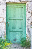 Green door. A weathered green door in a white wall Stock Photo