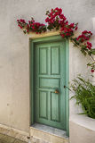 Green door in the white eall with little lpurple flouers Stock Images