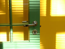 Green door and yellow wall. Shades running across them Royalty Free Stock Photo