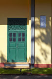 Green door and yellow wall Royalty Free Stock Image