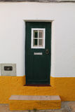 Green door. In a yellow and white facade Royalty Free Stock Images