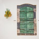 Green doors with flowers in the pot on a white wall. Close up stock photos