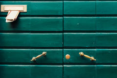 Green doors with newspaper. And metallic handles Royalty Free Stock Images