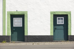 Green doors over a white facade building and street. Azores Royalty Free Stock Image