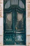 Green doors. Wood texture. Old shabby, irradiated paint. Stock Photos
