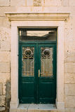 Green doors. Wood texture. Old shabby, irradiated paint. Royalty Free Stock Photos