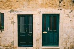 Green doors. Wood texture. Old shabby, irradiated paint. Stock Photo