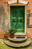 Green doorway in the village of Vernazza, Italy. A paint-chipped green doorway pops out of a narrow alley in the cliffside village of Vernazza in the Cinque Stock Images