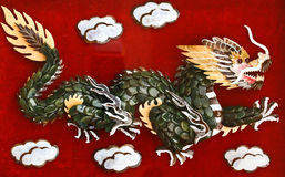 Green dragon. On the red background Stock Photography
