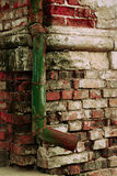 Green drainpipe at brick wall Royalty Free Stock Photo