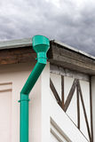 Green drainpipe on wall of house Stock Photos