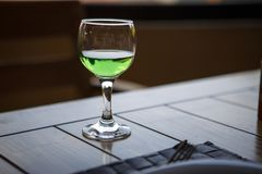 Green drink in the glass is on a wooden table. royalty free stock photos