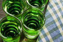 Green drink in shots on wooden table Royalty Free Stock Photography