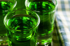 Green drink in shots on wooden table Royalty Free Stock Image