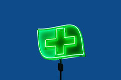 Green drugstore cross. Nigt illuminated advertisment of drugstore, isolated on dark blue foreground stock photography