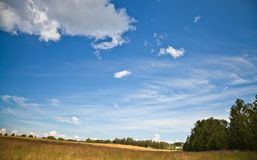 Green dry field under beautiful bright cloudy sky Stock Photo
