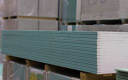 Green drywall sheets are in stock lot. Green drywall sheets are in stacks in the warehouse lot at the hardware store closeup stored Royalty Free Stock Photo