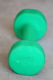 Green Dumbbell. Close up view of a green dumb bell laying on a concrete slab Royalty Free Stock Photo