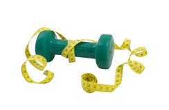 Green dumbbell and yellow tape measure on a white Royalty Free Stock Images