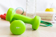 Green dumbbells, water bottle, apple, jump rope and a towel. Set for sports. Royalty Free Stock Images