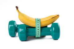 Green dumbell and banana. The green dumbell and yellow banana on white background Stock Photos