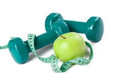 Green dumbell with measuring tape Royalty Free Stock Photography