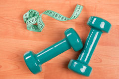 Green dumbell with measuring tape Stock Photo