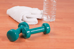 Green dumbells on wooden background Stock Images