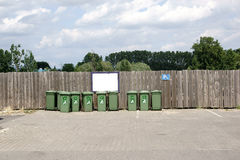 Green dumpster in front of wooden wall Stock Image