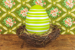 Green dyed big easter egg in a bird nest on a wooden table Stock Photo