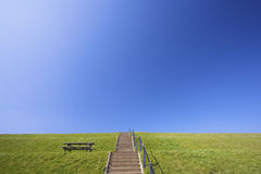 A green dyke in spring with a blue sky Royalty Free Stock Photography