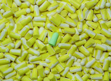 Green ear plug on the several yellow ear plug. Stock Photo