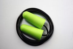 Green earplug noise protection for occupational safety on a white background. Close-up. Green earplug noise protection for occupational safety on a white stock photos
