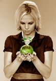 Green Earth. Metaphor with young woman holding the earth with growing plant Royalty Free Stock Photo
