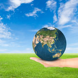 Green Earth concept. Hand holding earth against green field and blue sky background.Elements of this image furnished by NASA Royalty Free Stock Photos